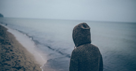 Sad woman hoodie beach